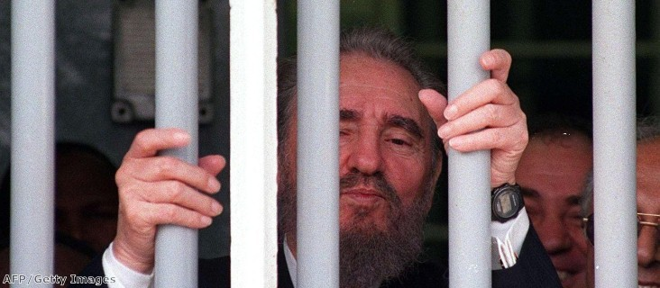 Fidel Castro peers out of the bars of Nelson Mandela's former cell on Robben Island during a recent visit.